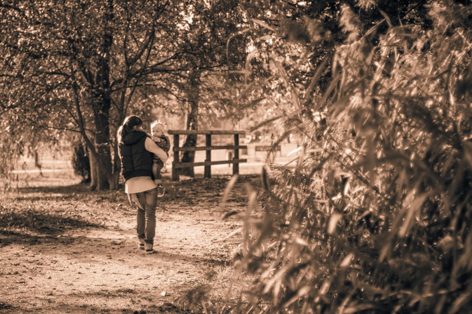 Mutter trägt Sohn einen Kieselweg entlang, Sepia-Filter, Schilf, Totale
