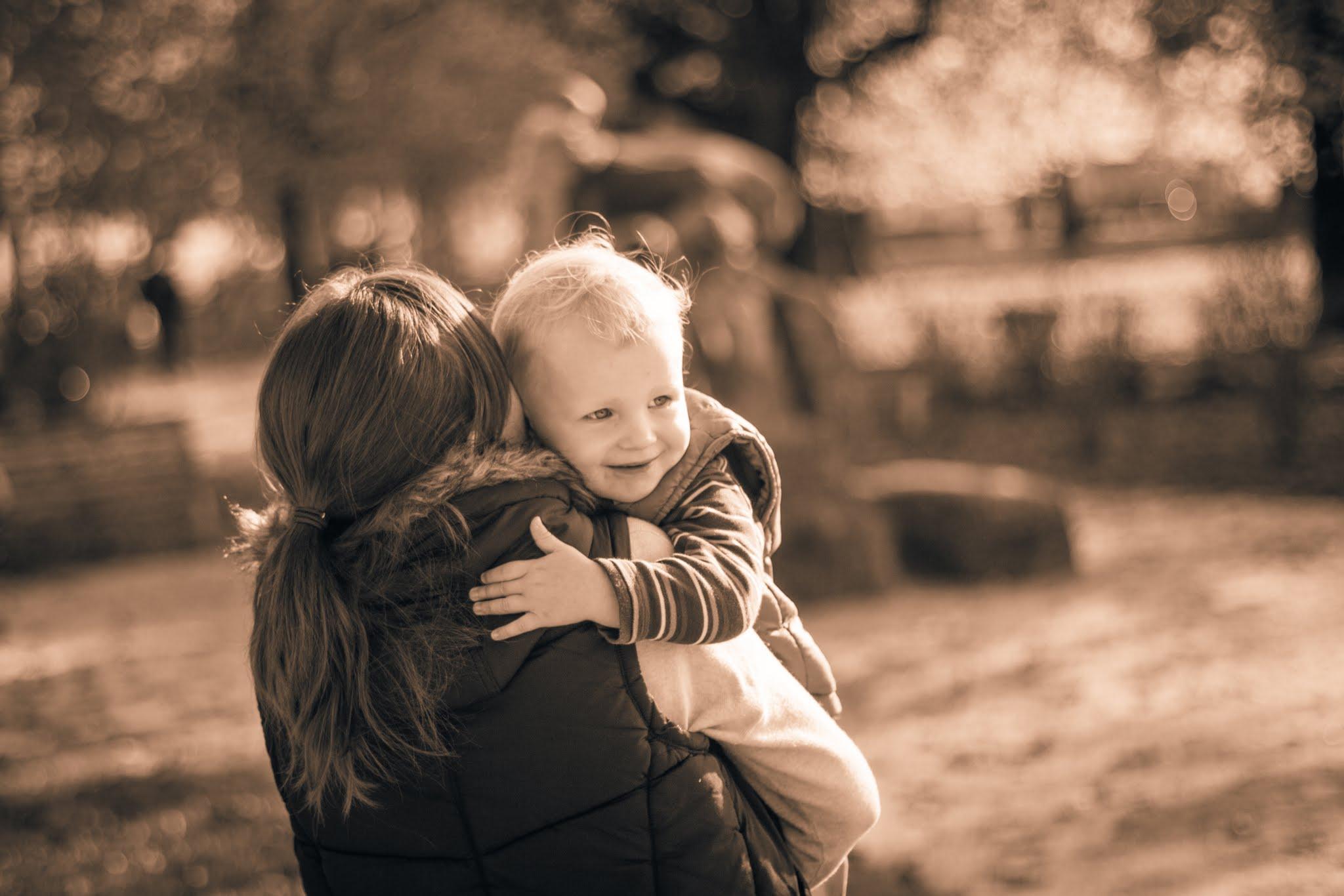 Mutter trägt Sohn einen Kieselweg entlang, Sepia-Filter, Nahaufnahme