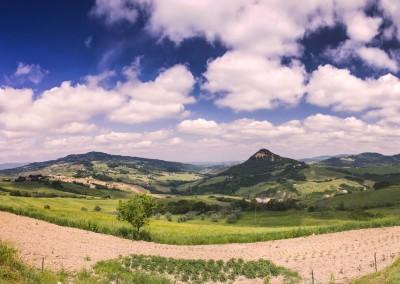 Wolkiges Panorama von toskanischem Hügelland mit Anbaufläche im Vordergrund, 180 Grad