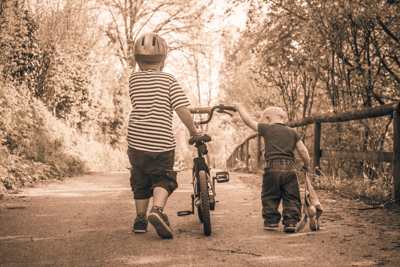 Zwei Brüder, die gemeinsam ein Fahrad einen schattigen Gehweg entlang schieben, Sepia-Filter, Totale