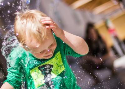 Junge läuft voll bekleidet durch Wasserstrahl